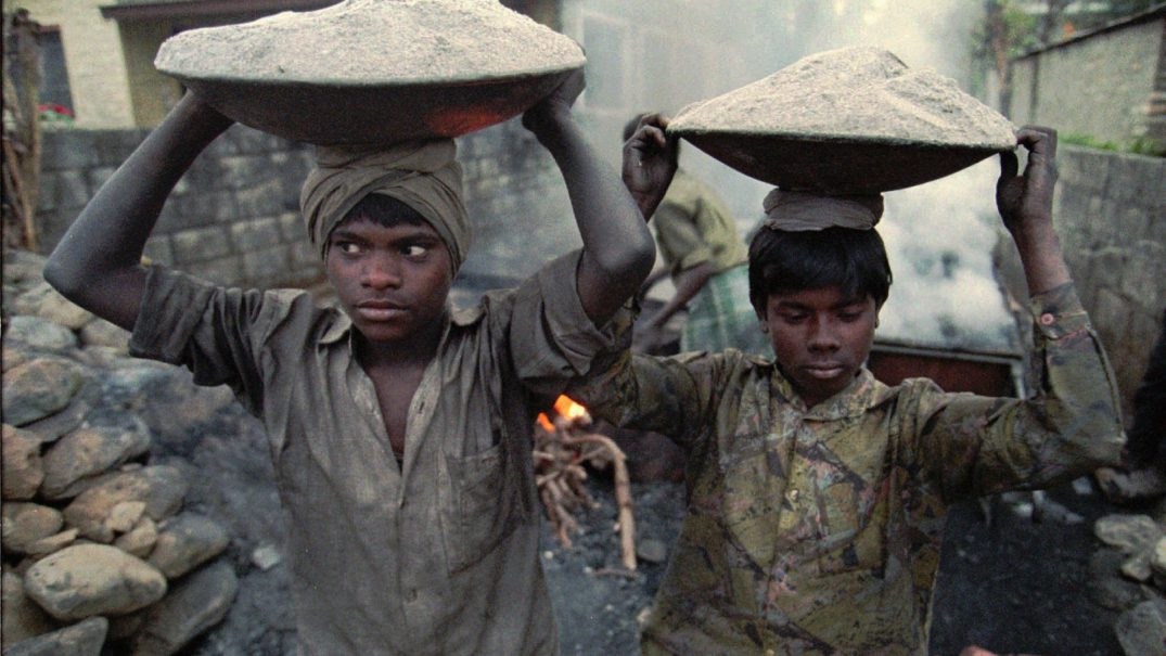 "Child laborers carry fine gravel to make asphalt while constructing ""tourist roads"" in Pokhara, Nepal Dec. 26, 1996. They work for up to 16 hours a day and earn less than $1. According to UNICEF reports, children are used because they are easier to handle, often working in extremely hazardous conditions without questioning authority."